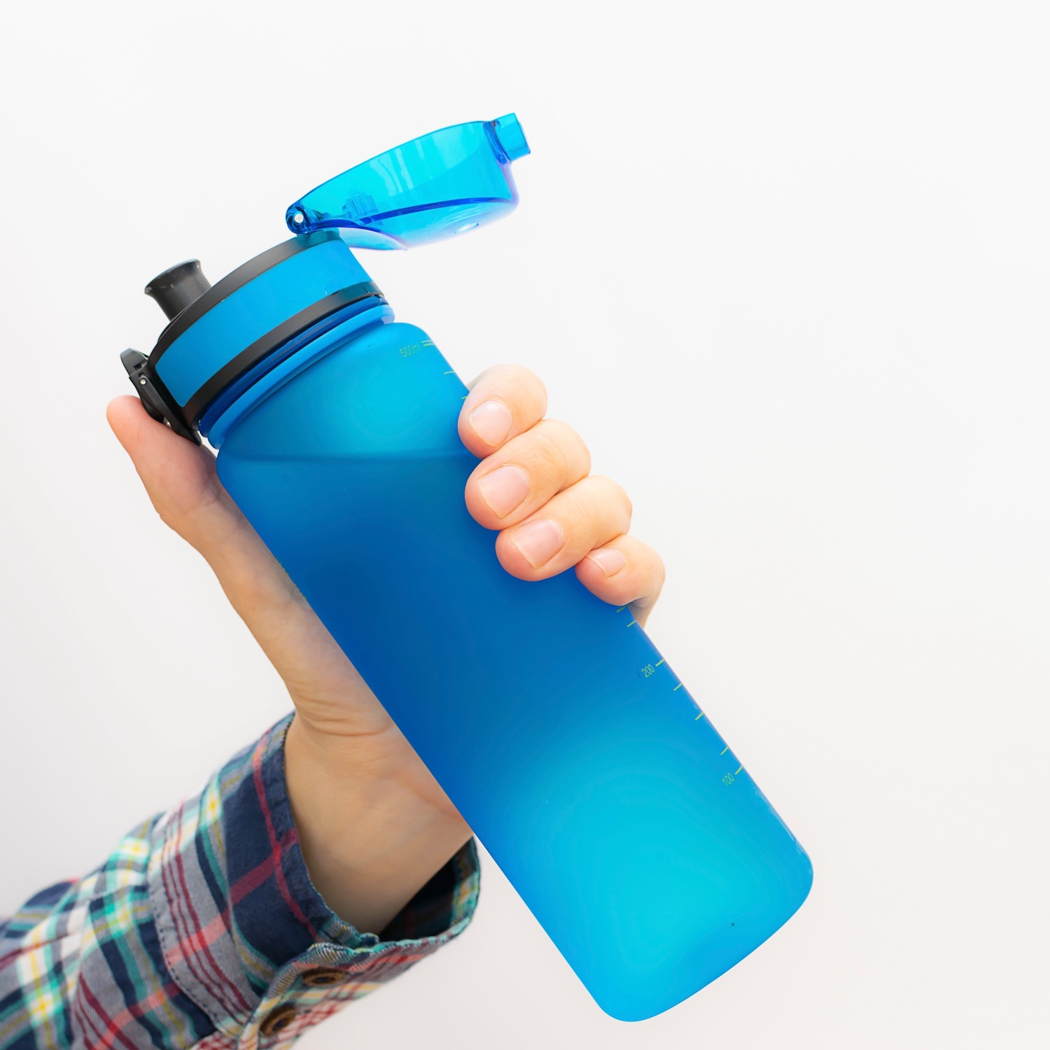 Creative composition with woman's hand holding bright blue plastic free reusable bottle  on white background with copy space. Ecology protection concept. BPA free materials. Zero waste concept.