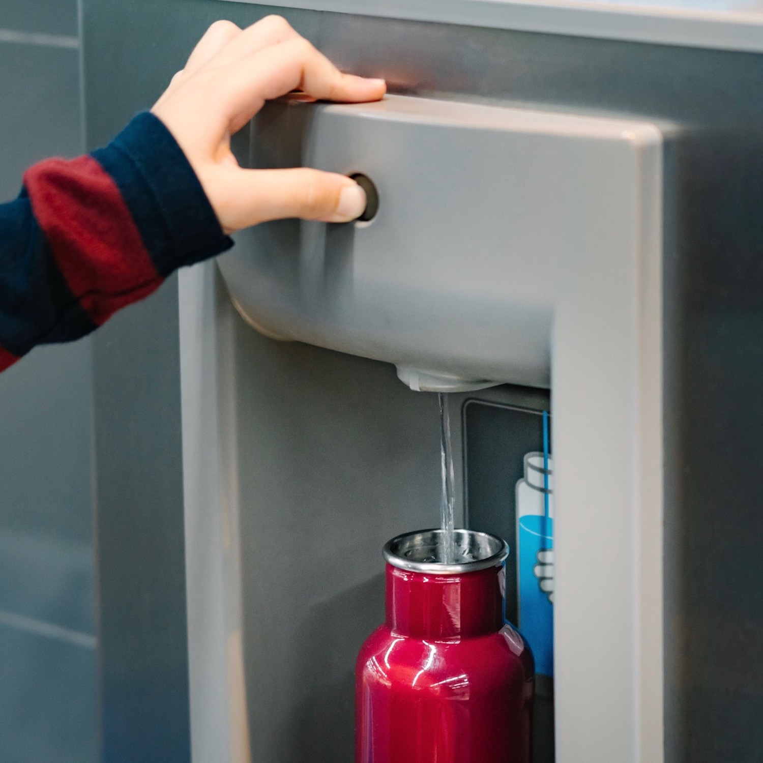 Hand of a traveler pressed the button of drinking water filling station at the Airport, fill up the reusable water bottle.  Eco friendly, Environmental awareness, No Plastic, Clean water, Zero waste.